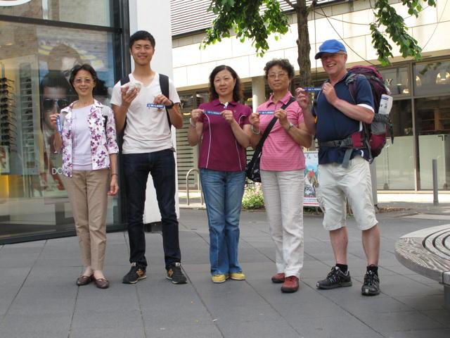 """Familie Lee aus Taiwan in der Outlet-City Metzingen gemeinsam mit Philipp und unseren """"100 % Heimat"""" Anhängern. Foto: Zenke"""