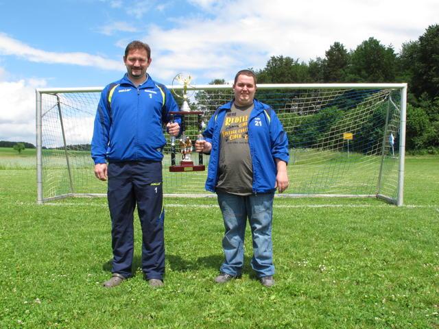 Roland Heinzelmann (links) und Jochen Betz sind zwei von 13 Sportsfreunden, die das Elfmeter-Turnier in Steinhilben organisiert haben. Zwischen ihnen zu sehen ist der Wanderpokal für die Sieger. Foto: Zenke