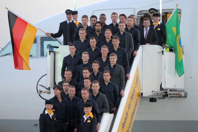 """Gruppenbild mit Damen: Unsere Nationalmannschaft vor dem Abflug mit einer Maschine der """"Fanhansa"""" in Frankfurt/Main. Foto: Fredrik von Erichsen/dpa"""