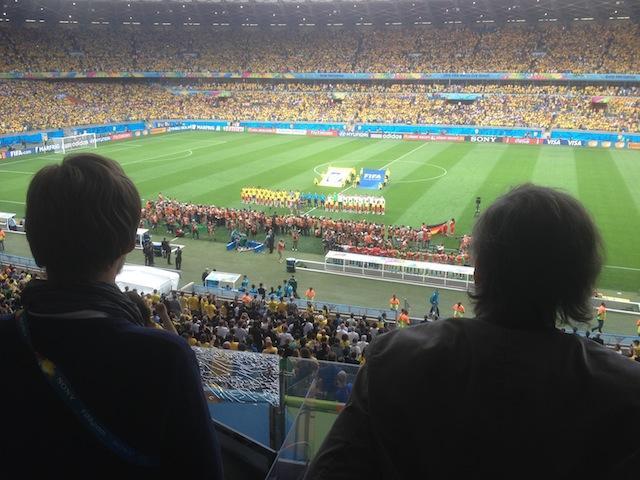 Die deutsche und die brasilianische Mannschaft bei der Nationalhymne in einem Stadion in Gelb. Foto: pr